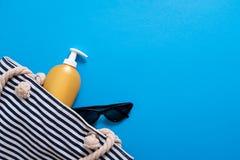Composición del verano Bolso pelado de la playa con crema y gafas de sol del bronceado Concepto de las vacaciones de verano, cosm imagen de archivo libre de regalías