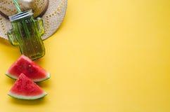 Composición del verano con la sandía, el sombrero y el envase para los jugos en fondo amarillo Concepto de verano Copie el espaci foto de archivo