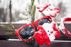 Composición divertida con las gafas de sol rojas, accessor del invierno de la Navidad Foto de archivo
