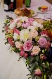 Composición en la tabla de la boda en los tonos blancos y rosados Peonías y rosas Imagen de archivo