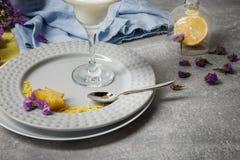 Composición estética Flores púrpuras y tela colorida en un fondo ligero de la tabla Una placa con leche y pétalos Foto de archivo