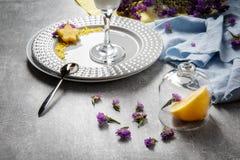 Composición estética Flores púrpuras y tela colorida en un fondo ligero de la tabla Una placa con un vidrio y frutas Fotos de archivo