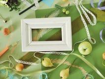 Composición estacional decorativa de frutas, de la decoración, de verdes y de un bastidor blanco en el papel entonado verde fotografía de archivo libre de regalías