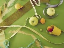Composición estacional decorativa de la fruta, decoración, verdor en el papel teñido verde foto de archivo libre de regalías