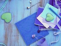 Composición estacional del verano de un par de corazones del fieltro, de papel con un lápiz, de cuadernos y de decoración imagen de archivo