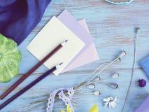 Composición estacional del verano de verduras, del papel con un lápiz y de la decoración en un fondo azul foto de archivo