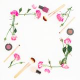 Composición femenina con las rosas y los cosméticos rosados en el fondo blanco Concepto de la belleza, marco floral Endecha plana Fotos de archivo