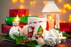 Composición festiva de la Navidad - una taza con Santa Klais, las tortas, las velas, las ramas del acebo, las bayas y los regalos Imágenes de archivo libres de regalías