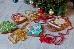 Composición festiva Tortas de miel con las imágenes esmaltadas que ponen bajo rama de árbol de la empanada en la tabla de madera  Foto de archivo