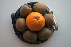Composición formada redonda de una naranja y de kiwis en un disco azul decorativo Imágenes de archivo libres de regalías