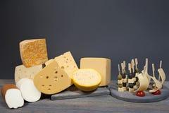 Composición gastronómica de diversos tipos de queso y de pinchos con los aperitivos en la tabla de madera Imágenes de archivo libres de regalías
