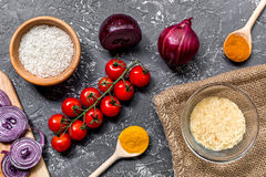 Composición hecha en casa de los ingredientes de la paella con el arroz, tomate, cebolla en la opinión superior del fondo oscuro  Fotografía de archivo