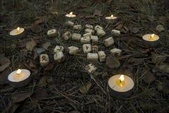 Composición hermosa de Halloween con las runas, el cráneo, el tarot y las velas en la hierba en ritual oscuro del bosque del otoñ Imagen de archivo libre de regalías