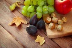 Composición otoñal, cosecha, frutas - setas, manzanas, ciruelos, hojas, uvas, nueces, humor del otoño fotos de archivo