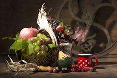 Composición pintoresca del otoño con la cesta, frutas, calabaza, taza Fotografía de archivo