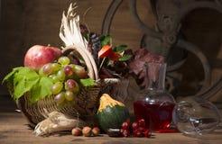 Composición pintoresca del otoño con la cesta, frutas, calabaza, taza Foto de archivo libre de regalías