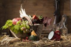 Composición pintoresca del otoño con la cesta, frutas, calabaza, triunfo Fotos de archivo libres de regalías