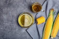 Composición plana de la endecha con la cristalería del aceite de maíz y de las mazorcas frescas imagen de archivo
