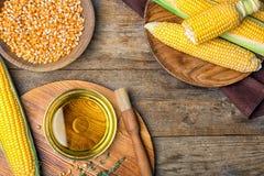 Composición plana de la endecha con el cuenco de aceite de maíz, mazorcas imagen de archivo