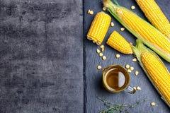 Composición plana de la endecha con el jarro de aceite de maíz y de mazorcas frescas imágenes de archivo libres de regalías