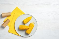 Composición plana de la endecha con las mazorcas de maíz en el fondo de madera blanco fotos de archivo libres de regalías
