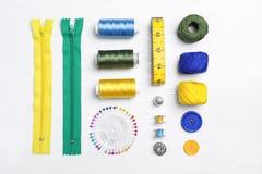 Composición plana de la endecha con los hilos de coser y los accesorios en fondo de madera Fotografía de archivo