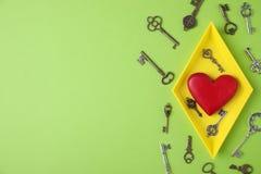 Composición puesta plana con diversas llaves y corazón decorativo en fondo del color fotos de archivo