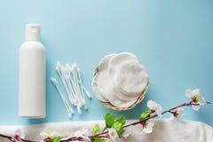 Composición puesta plana con la botella, esponjas y cojines de algodón, flores y toalla blancos en fondo azul concepto del cuidad imagen de archivo libre de regalías