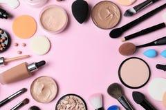Composición puesta plana con la fundación de la piel, el polvo y los accesorios de la belleza en fondo del color foto de archivo libre de regalías