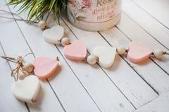 Composición puesta plana con las barras hechas a mano del jabón en la forma de corazones en el fondo de madera blanco fotos de archivo