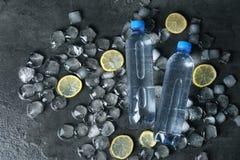 Composición puesta plana con las botellas de agua, de rebanadas del limón y de cubos de hielo en oscuridad imagen de archivo