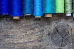 Composici?n puesta plana con los hilos de coser coloridos en fondo de madera Concepto de la manera Copie el espacio imagen de archivo