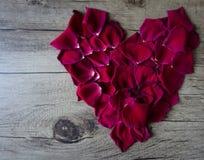 Composición puesta plana con los pétalos color de rosa que forman un corazón que sale del SP imagenes de archivo