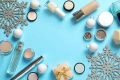 Composición puesta plana con los productos de maquillaje y decoración de la Navidad en fondo del color fotos de archivo