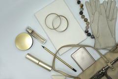 Composición puesta plana de los productos de belleza y bolso para las mujeres Pastel y colores oro en el fondo blanco imagen de archivo libre de regalías
