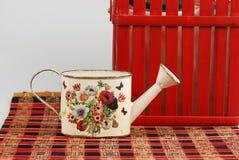 Composición roja con un pequeño cubo para las flores de riego imagen de archivo libre de regalías