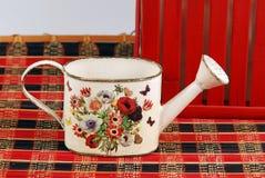 Composición roja con un pequeño cubo para regar flor-más cercano imágenes de archivo libres de regalías