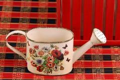 Composición roja con un pequeño cubo para regar flor-más cercano fotografía de archivo libre de regalías
