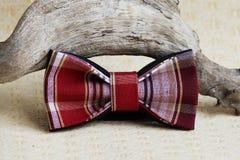 Composición: Rojo a cuadros extravagante con una corbata de lazo negra, curva de madera del palillo en un fondo beige Imagenes de archivo