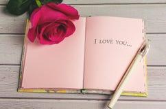 Composición romántica con el fondo color de rosa del día de las flores y de tarjetas del día de San Valentín del St del texto te  Fotografía de archivo