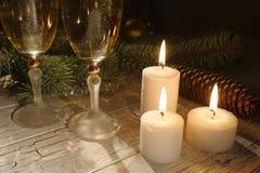 Composición romántica del Año Nuevo de las tres velas que brillan intensamente cerca de los vidrios de champahne en el fondo de l Foto de archivo libre de regalías