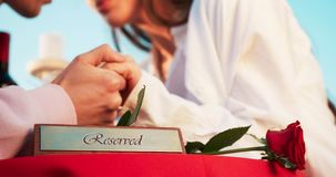 Composición romántica Placa reservada y rosa del rojo en la tabla en el fondo borroso de los pares en amor blando almacen de video