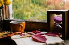 Composición triste del otoño de la taza de café, libro, hojas coloridas imagen de archivo libre de regalías