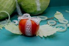 Composición vegetal, aún vida 3 de los tomates rojos, hojas de la col verde fresca, primer en un backgr Foto de archivo