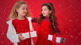 Composición video con nieve que cae sobre niños con las cajas de regalo en manos almacen de metraje de vídeo