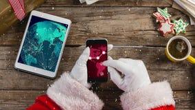 Composición video con nieve sobre el escritorio con santa que sostiene el teléfono elegante