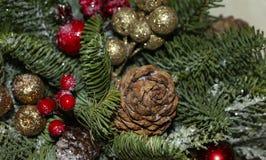 Composici?n de la Navidad de las ramas del pino, de las decoraciones de oro de la Navidad, de las bayas rojas y de la nieve artif foto de archivo libre de regalías
