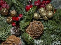 Composici?n de la Navidad de las ramas del pino, de las decoraciones de oro de la Navidad, de las bayas rojas y de la nieve artif fotos de archivo libres de regalías