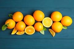 Composici?n puesta plana con las naranjas y las hojas maduras en fondo de madera Visi?n superior imagenes de archivo