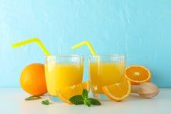 Composici?n puesta plana con los zumos de naranja frescos, el juicer de madera, la menta, las naranjas y el juicer de madera en l foto de archivo